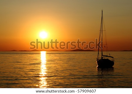 Gold romantic sunset with silhouette of yacht - stock photo