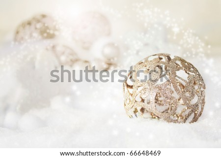 Gold rustic Christmas baubles in the snow. - stock photo