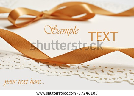 Gold satin ribbon on decorative cream colored paper with copy space.  Macro with extremely shallow dof. - stock photo