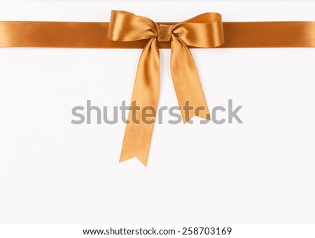 Gold satin ribbon with a bow on a white background - stock photo