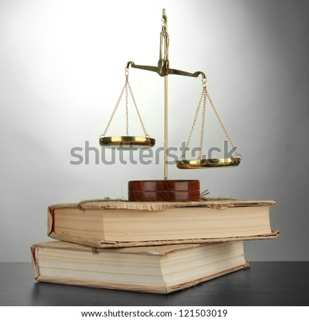 Gold scales of justice and books on grey background - stock photo