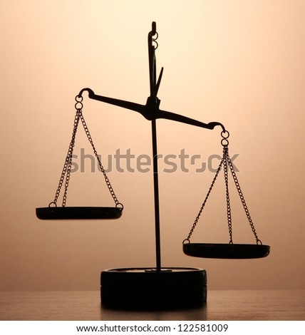 Gold scales of justice on brown background