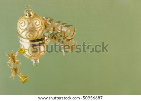 gold scroll pattern Christmas bauble on soft green background with copyspace - stock photo