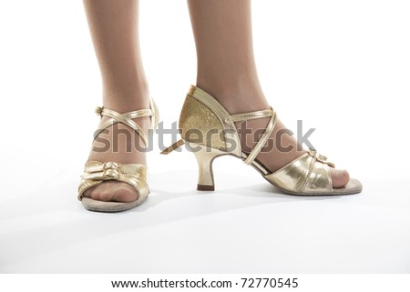Gold shoes standing at the young dancer of the girl.  White background - stock photo