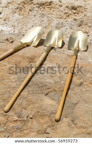 Gold shovels lay at a construction site after a ground breaking ceremony. - stock photo