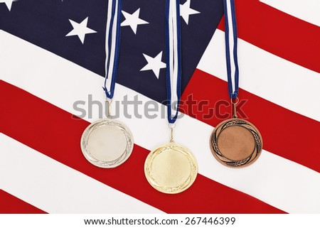 Gold silver and bronze medal on american flag - stock photo