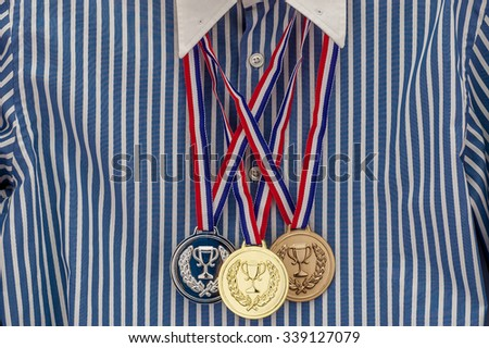 Gold, silver, bronze blank award medals on the blue and white cotton shirt, concept of success in business - stock photo