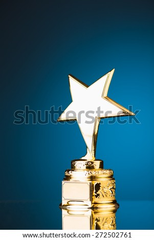 gold star trophy against blue background - stock photo