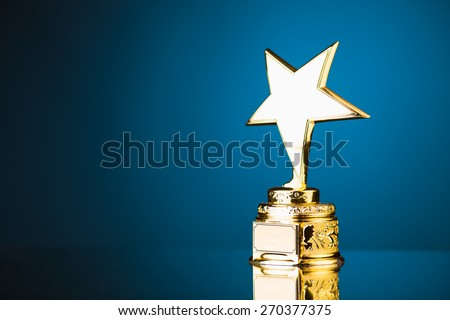 gold star trophy award against blue background - stock photo