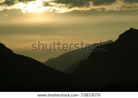 Gold sunset in clouds with silhouette of mountains. - stock photo