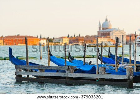 Gold sunset with gondolas docked in Grand Canal, Venice, Italy. Bright sunny panorama view of Grand Canal with gondola and church. Beautiful photo background of the venetian canal in the morning.