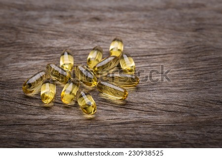 Gold tablets of vitamin E. On a wooden texture. - stock photo