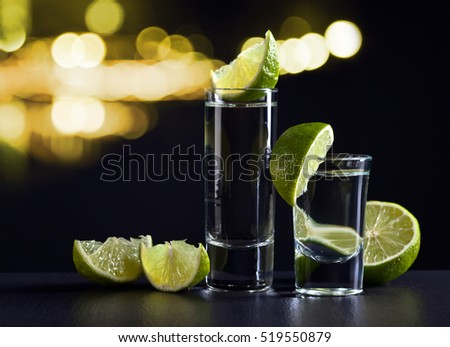 Gold tequila and lime on a dark background