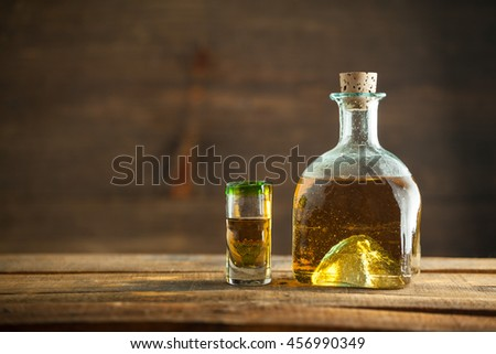 Gold tequila in glass on wood table. Selective Focus. Blurred background.