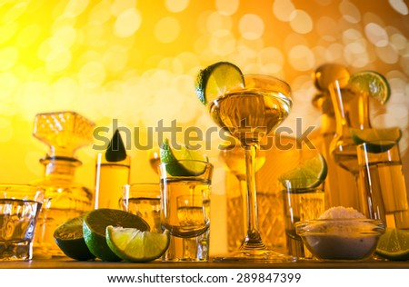 gold tequila , lime and salt , focus on foreground - stock photo