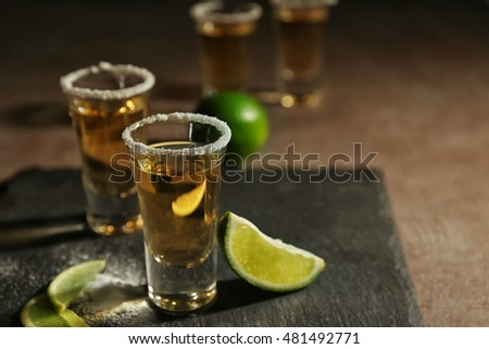 Gold tequila shots with lime slices and salt on grey board