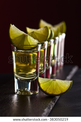 Gold tequila with lime on a dark background