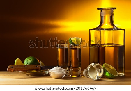 gold tequila with salt and lime on wooden table - stock photo