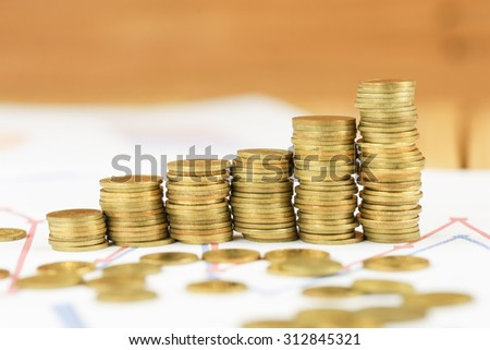Gold Thai coin on financial graph report on wood table