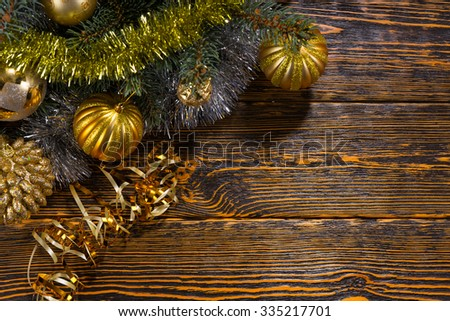 Gold themed Christmas decorations with assorted gold baubles arranged on a pine branch with tinsel, corner arrangement over a rustic wood background with copyspace - stock photo