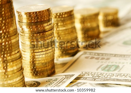 gold towers of coins on the paper dollars - stock photo