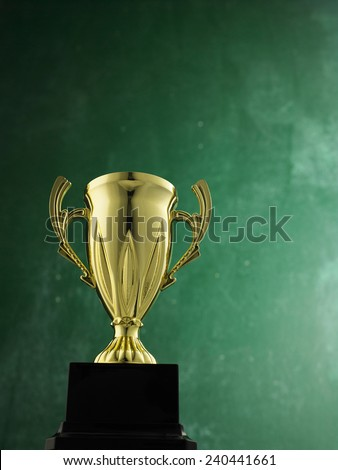 gold trophy against black board - stock photo