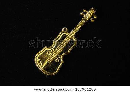 Gold Violin Instrument Figurine on a Colored Background