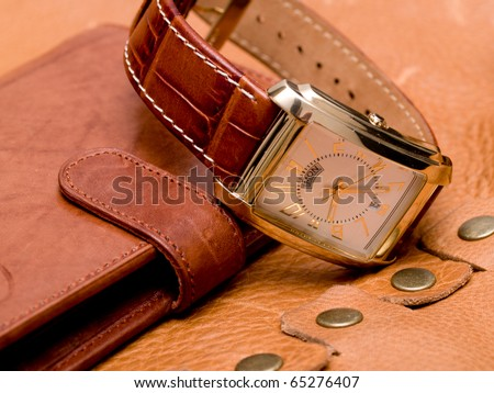 gold watch lying on a leather purse - stock photo