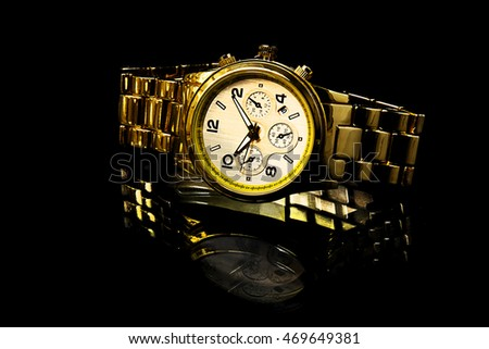 gold watch with reflection on black background