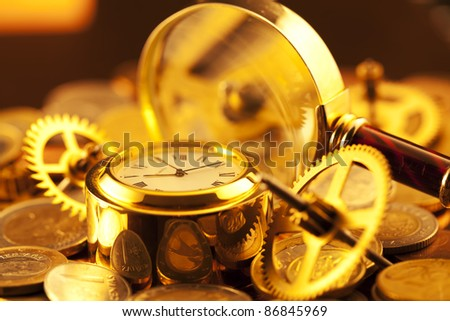 gold watches, coins, gears and magnifying glass - stock photo