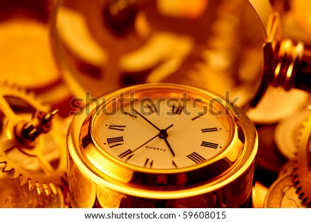 gold watches, coins, gears and magnifying glass on the mirror surface - stock photo