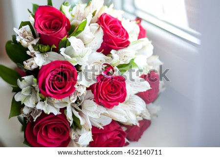 Gold wedding rings lie on a bouquet of roses bride, wedding attributes