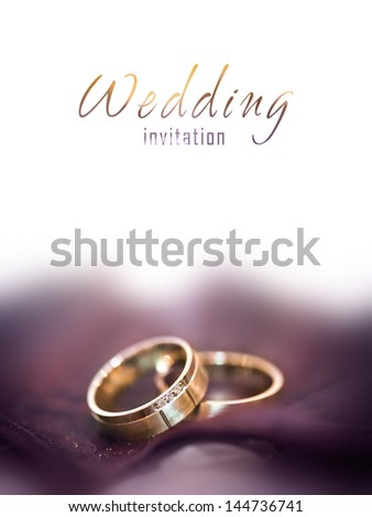 Gold wedding rings on a big brown leaf - stock photo