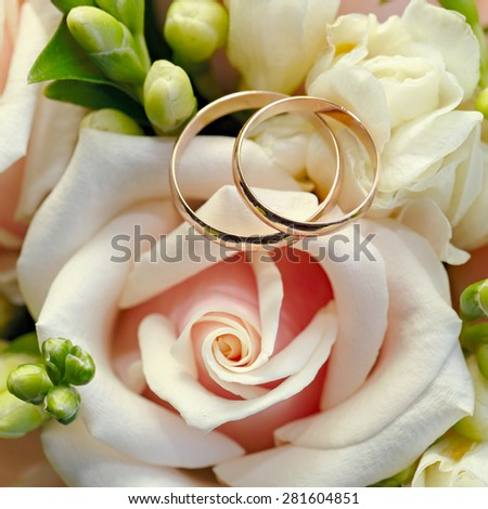 Gold wedding rings on a bouquet of flowers for the bride  - stock photo