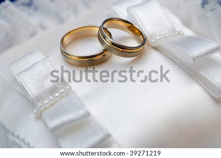 Gold wedding rings on a satiny pillow