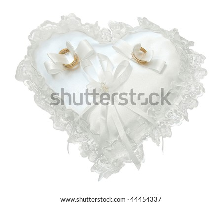 Gold wedding rings on a satiny pillow in heart form - stock photo