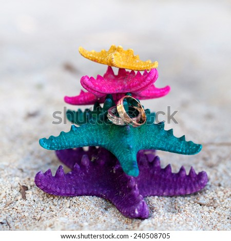 Gold wedding rings on color starfishes on white beach. Wedding Vacation concept - stock photo