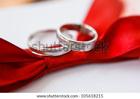 gold wedding rings on red - stock photo