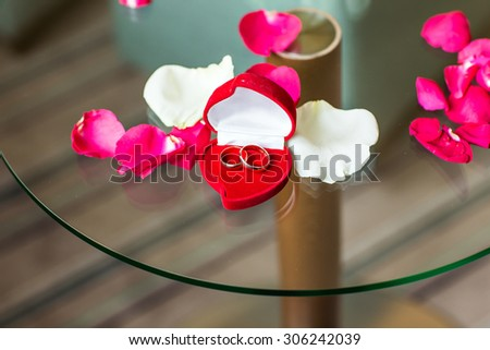 gold wedding rings on the rose petals - stock photo