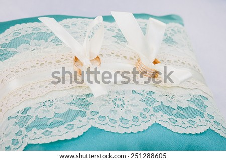 gold wedding rings on the turquoise pincushion - stock photo