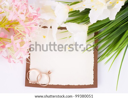 Gold wedding rings with banner add and bouquet of flowers