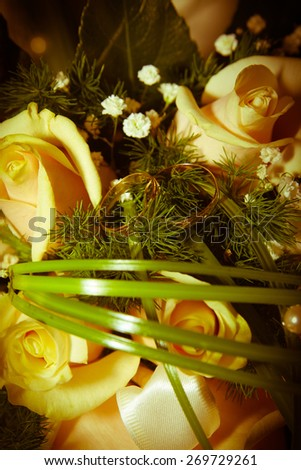 Gold wedding rings with bouquet of flowers - stock photo