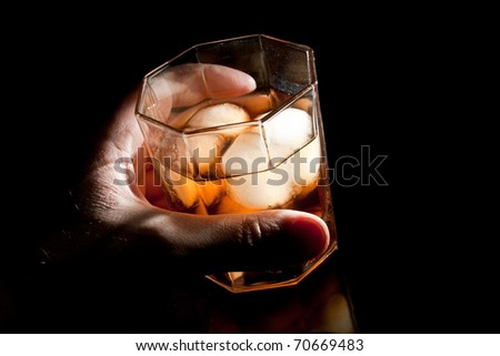 Gold whiskey on the rocks in alcoholic's hand - stock photo