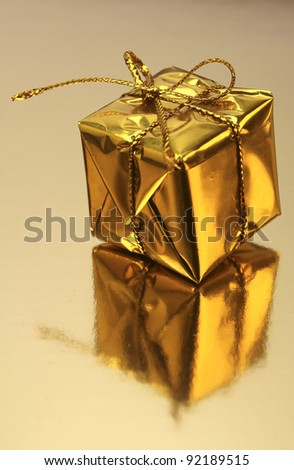 Gold wrapped gift on a golden background - stock photo