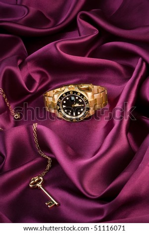 Gold wrist watch lying on the silk cloth with vintage gold key. - stock photo