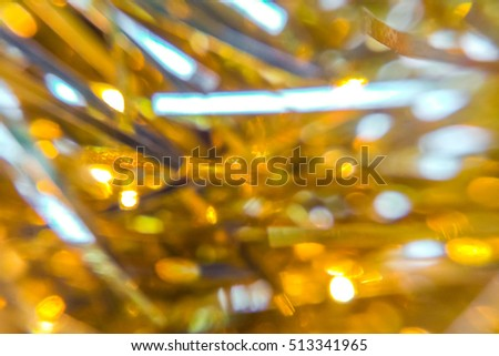 Gold-yellow blurred tinsel, Christmas decorations closeup, abstract background or texture