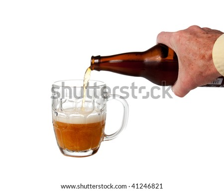 Golden ale being poured from brown bottle into half full english pint mug