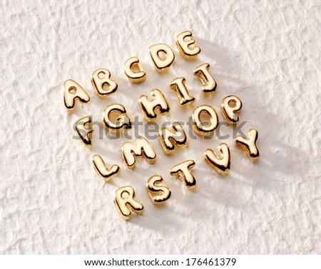 golden alphabet letters on rough paper - stock photo