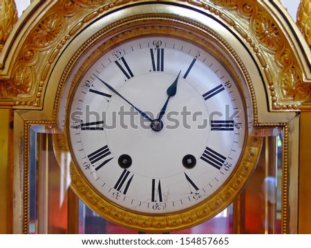 Golden analogue wall clock with Roman numbers