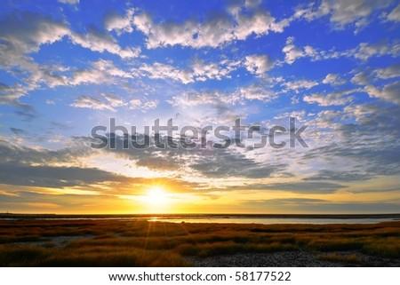 Golden and blue sunset near the coast - stock photo